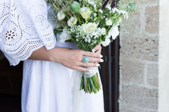 The ring with blue stone on the bride's finger. Bride in white wedding dress holds a wedding bouquet outdoor. Royalty Free Stock Images