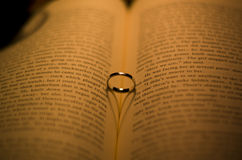 Ring in the book with a Heart-shaped shadow Royalty Free Stock Photo