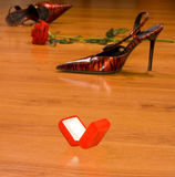 Ring box on the floor. Opened ring box on the floor in background with women red shoes stock photography