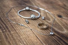 Ring and bracelet and earrings and chain with pendant on wooden background stock image