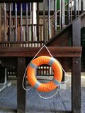Ring buoy hanging on the wooden staircase near swimming pool in the hotel resort for emergency Royalty Free Stock Images