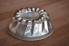 Ring cake pan on wood table Royalty Free Stock Images