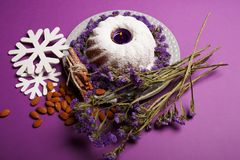 A plate with a ring cake, lit candle, cinnamon, almond and snowflakes on a bright violet background, top view. A ring cake sprinkled with powdered sugar, a Royalty Free Stock Photo