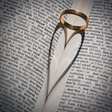 Ring casting a heart-shaped shadow in a book. Royalty Free Stock Image
