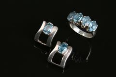Ring and earring with aquamarine stone. A close up on an aquamarine jewel on a dark background stock photos