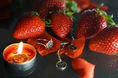 Ring and earrings with the symbol of bdsm lying among the strawberries on the black table top view. Nobody royalty free stock photo