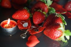 Ring and earrings with the symbol of bdsm lying among the strawberries on the black table top view. Nobody royalty free stock photos