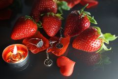 Ring and earrings with the symbol of bdsm lying among the strawberries on the black table top view. Nobody royalty free stock images