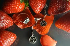 Ring and earrings with the symbol of bdsm lying among the strawberries on the black table top view. Nobody royalty free stock image