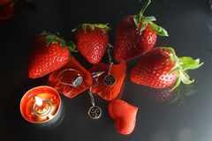 Ring and earrings with the symbol of bdsm lying among the strawberries on the black table top view. Nobody royalty free stock photography