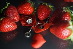 Ring and earrings with the symbol of bdsm lying among the strawberries on the black table top view. Nobody stock image