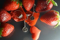 Ring and earrings with the symbol of bdsm lying among the strawberries on the black table top view. Nobody stock photo