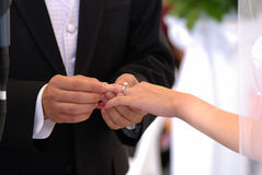 Ring Exchange. He put the wedding ring on her finger Royalty Free Stock Photos