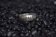 Ring faith. A simple silver ring with faith engraved in it on a simple black stone background for contrast Stock Image