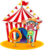 A ring of fire and a clown in front of a circus tent Stock Images