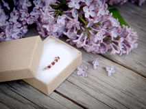 Ring in gift box and lilac on wood Royalty Free Stock Photography