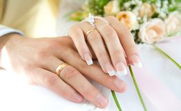 Ring & hands over white and flowers, wedding day. Ring and hands over white and flowers, wedding day Royalty Free Stock Image