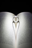 Ring Heart Shadow. Ring lit under dim light to create heart shaped shadow. Underlying book is an Italian Novel Stock Images