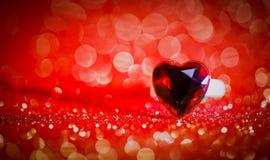 Ring Hearts auf rotes bokeh Texturfunkelnhintergrund Roter heart-shaped Schmucksachegeschenkkasten und eine rote Spule auf einem  Lizenzfreies Stockfoto