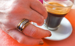Ring on her finger, espresso in a cup. Royalty Free Stock Photos