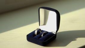 Ring in het vakje op houten lijst voorraad Trouwringen in een geval op de lijst die door zonlicht wordt verlicht royalty-vrije stock foto's