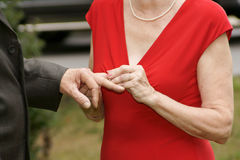 With this ring, I thee wed. Bride places ring on the groom's finger uniting them for eternity Royalty Free Stock Image