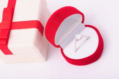 Ring ina red box next to a gift. Diamond engagement ring in a red box Stock Photo