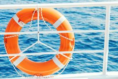 Ring life buoy on boat. Obligatory ship equipment. Orange lifesaver on the deck of a cruise ship. Travel royalty free stock photography