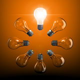 Ring of light bulbs with one lit up Stock Images