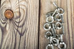 Ring nuts with bolts, zinc plated on wooden background royalty free stock photo