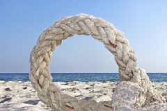 Ring of old rope on a seashore Stock Images