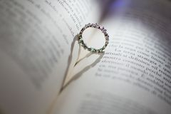 Ring between the pages of a book that projects a shadow in the shape of a heart stock photography