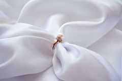 Ring with a pearl and brilliants and sateen. Ring with a pearl and brilliants and white sateen stock images