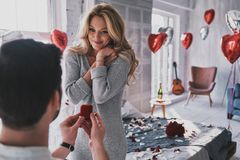 Ring is perfect! Attractive young woman looking at engagement ri. Ring is perfect! Attractive young women looking at engagement ring with smile while her Royalty Free Stock Photography