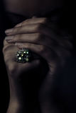 Ring of prayer. Studio portrait of model's hands with jewel ring in dramatic light Royalty Free Stock Image