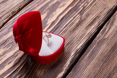 Ring for the proposal. Ring for the proposal in a red box. Diamond ring on a wooden background stock photo