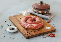 Ring of raw sausage on a cutting board with pepper Stock Photo