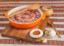 Ring of raw sausage on a cutting board with pepper Stock Images