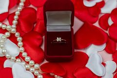 Ring in a red box and pearls on a background of hearts of red and white. Wedding ring in the box. stock photos