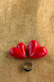 Ring with Red Hearts Over golden shiny fabric Stock Image