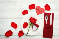 Ring with red rose on white plate. Silver ring with red rose on white plate and kitchen cutlery Stock Photo