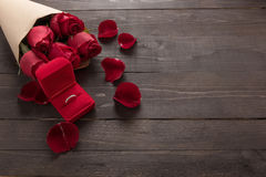 Ring is beside of the red roses flower on the wooden background Royalty Free Stock Images