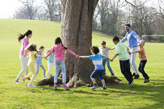 Ring -A -Rosie. A group of children with two adults holding hands and dance around the trunk of a tree stock images