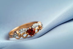 Ring with ruby on grey background Stock Photos