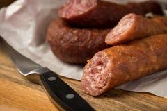 Ring Salami grisköttkorv med tyska Bierbeißer i vaxpapper med kniven på träbrädebakgrund för den Brotzeit matställen arkivfoton