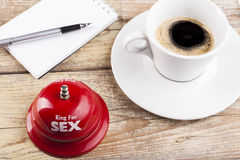 Ring For Sex. Bell on wood table with coffee and notepad inthe background Royalty Free Stock Image
