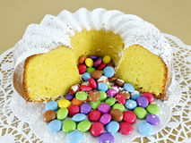 Ring-shaped sponge cake and colour-varied sugar-coated chocolate confectionery royalty free stock image