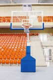 Ring and shield for playing basketball. Orange chairs stand in a row in a covered stadium Stock Photos