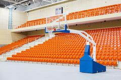 Ring and shield for playing basketball. Orange chairs stand in a row in a covered stadium. Stock Photography
