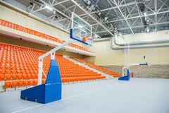 Ring and shield for playing basketball. Orange chairs stand in a row in a covered stadium. Stock Photos